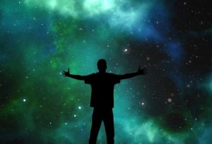 Person in silhouette opening arms to universe